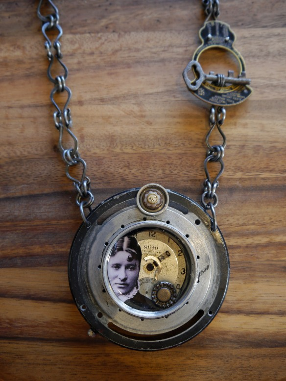 Vintage camera parts, watch face, vintage buttons, key, photograph, steel chain.